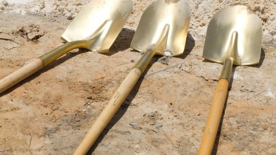 Gold shovels lay at a construction site after a ground breaking ceremony.